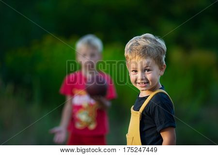 Cute little boy with hazel eyes playing with ball with friend and smiling on sunny summer day in countryside