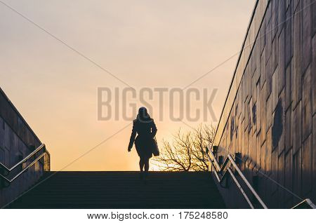 Silhouette of a lonely woman climbing the stairs from an underpass. Concept of loneliness in city life
