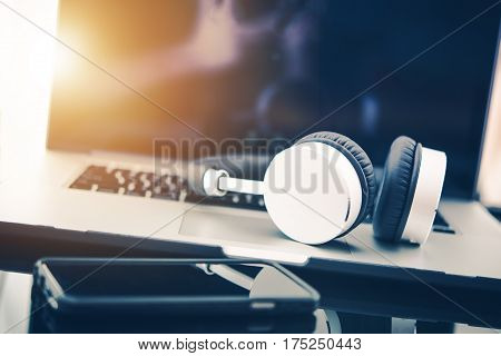 Computer in Business Concept. Laptop Computer Workstation with Wireless Headphones For Privacy and Sound Quality. Listening Relaxing Music While Working.