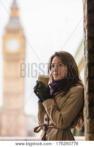 Thoughtful girl or young woman drinking coffee in a disposable cup by Westminster Bridge with Big Ben and The Houses of Parliament in the background, London, England, Great Britain