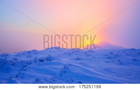 Sunrise enlightens sky mountain and trees standing in snowdrifts covered by frozen snow with yellow shine.