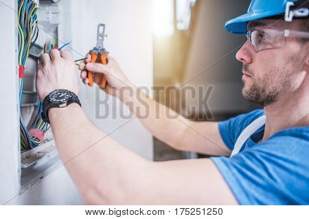 Electric Technician Job. Caucasian Professional Electrician in His 30s Finishing Electric Box Inside the Apartment.