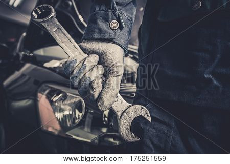 Fixing the Car Concept. Mechanic with Large Wrench is About To Start His Car Maintenance and Fix Work.