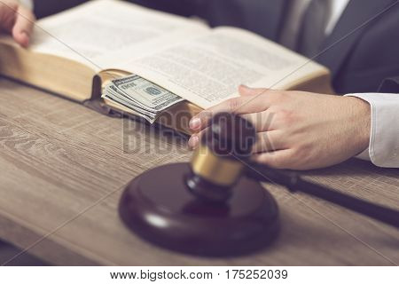Detail of corrupted judge sitting at his desk studying new laws and legislation. Selective focus