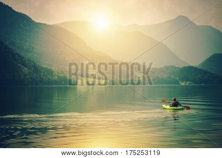 Lake Kayak Touring. Summer Recreations and Sport Photo Concept. Senior Sportsman in the Tour Kayak on the Lake.