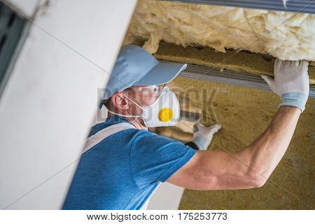 Mineral Wool Insulation by Professional Insulating Worker. Caucasian Construction Worker in His 30s.