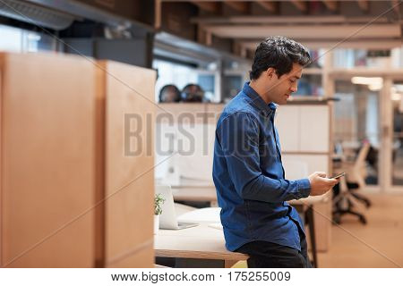 Casually dressed handsome young businessman reading a text message on his cellphone while standing alone by desks in a modern office