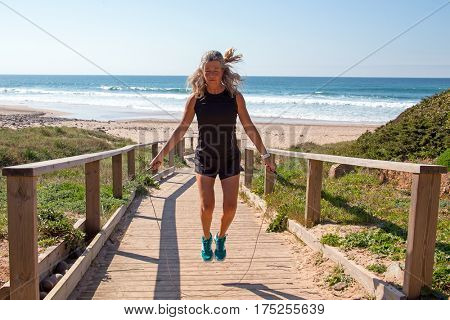 Mature woman exercising jumping rope at the beach