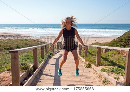 Mature woman doing jumping jacks with a jumping rope