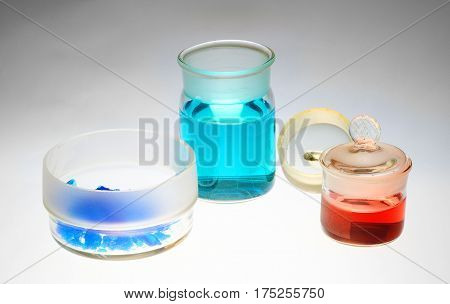 Chemical glassware weighing bottles with chemicals on gray background