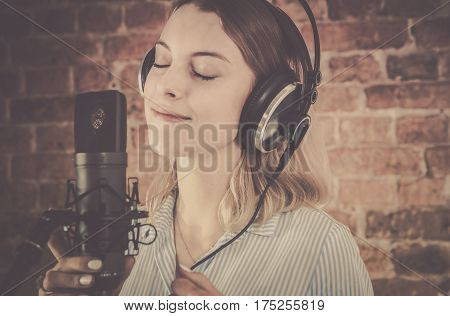 Voice Over Recording. Woman in Her 20s Recording Audio in the Professional Recording Studio.