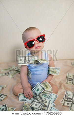 Cute baby boy in sunglasses playing with money, hundreds of dollars.