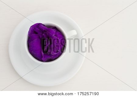 Fragrant morning coffee with violet flowers in a cup on a white wooden table