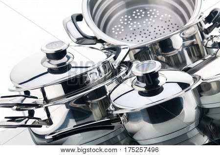 Set of chrome plated aluminum cookware - pots, pans, shot in studio on a white background