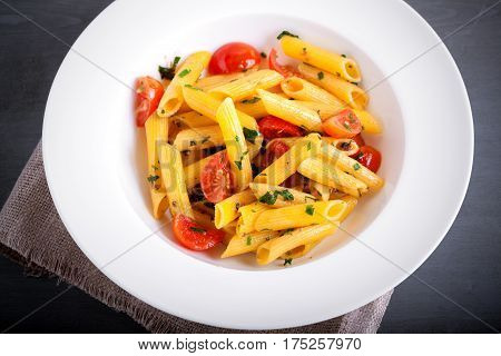 Penne with anchovy and tomato in a white plate