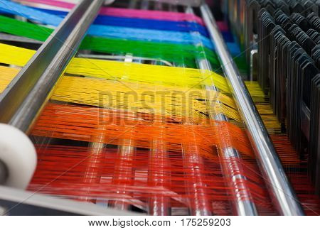textile industry machine with thread in lgbt colors