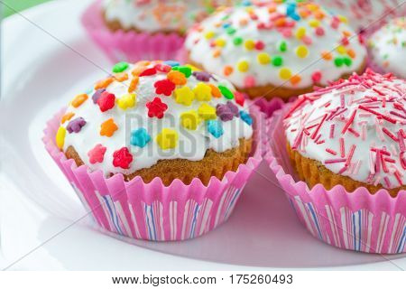celebrations colored cup cakes with glaze on a plate