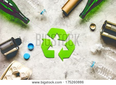 Eco concept with recycling symbol and garbage on stone table background top view