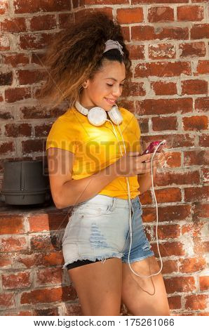 Portrait of Latin girl with headphones and CellPhones