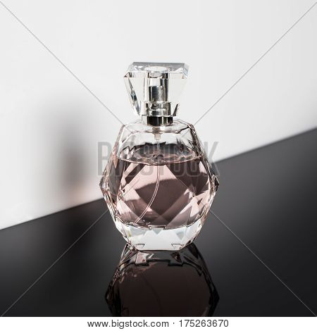 Perfume bottle with reflection on white background. Perfumery, cosmetics
