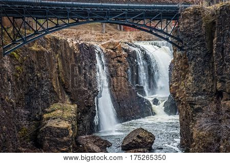 The Great Falls of Paterson framed by the steel arch bridge high above.