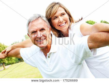 Happy smiling elderly seniors couple in park.