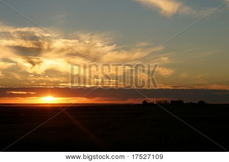 A praire sunset with a farm in the background.