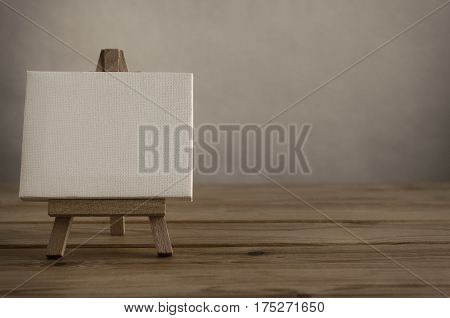 Close Shot of blank art canvas on easel standing to left of frame on wood plank floor as if in gallery or studio with empty wall behind and to the right.