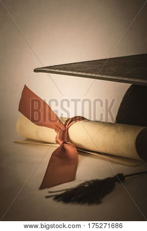 A rolled parchment scroll tied with red ribbon next to a black mortarboard. Low saturation brown hues and vignette for retro or vintage effect. Education or success concept.