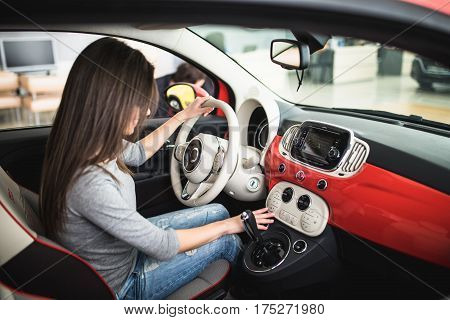 Woman driving new and modern car and use dashboard panel in car