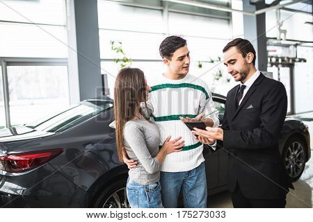 auto business car sale technology and people concept - happy couple with car dealer in auto show or salon