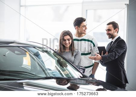 Beautiful couple choosing a car at the dealership talking to the salon manager