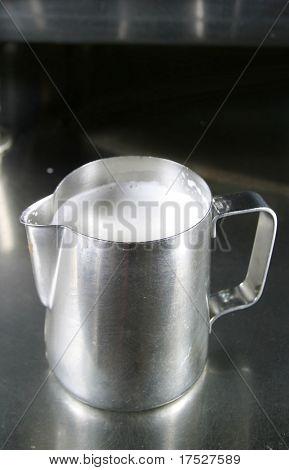Milk Steaming mug filled with warm milk