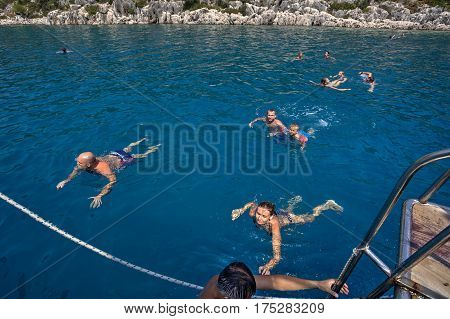 Antalya Turkey - 28 august 2014: Many vacationers are swimming in the Mediterranean Sea near the cruise boat.