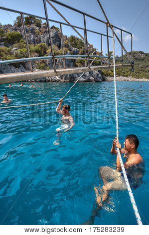 Antalya Turkey - 28 august 2014: Tourists swim in the sea holding on to the ropes of a pleasure yacht.