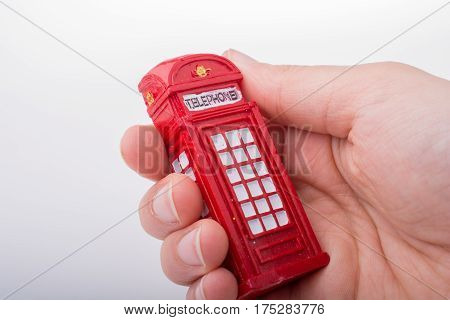 Hand Holding A Phone Booth On A White Background