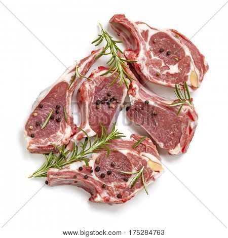 Raw lamb cutlets, top view, isolated, with rosemary and peppercorns.