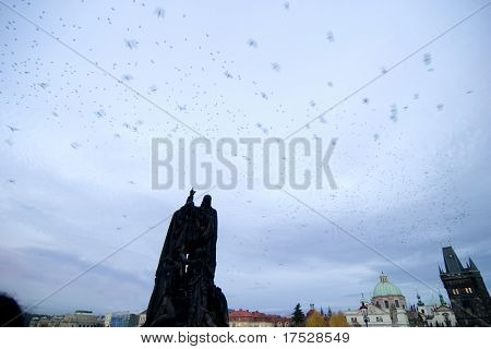 A large flock of birds swarming over a Charles Bridge Statue in Prague, Czech Republic in the early evening.