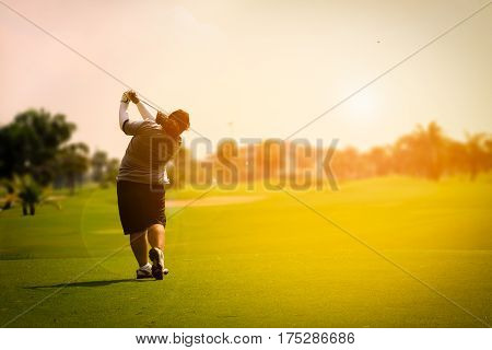 female golf player swinging golf on fairway during sunset with flare