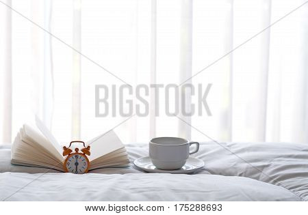 Alarm clock on bed with coffee and book in morning with sun light