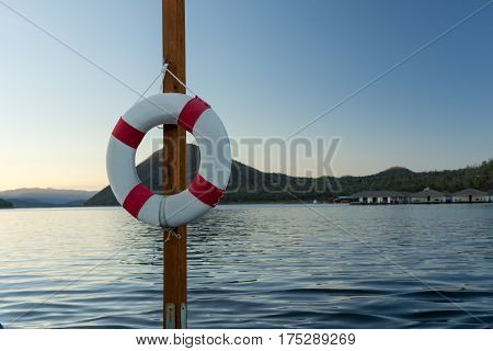 Red and White Lifebuoy on the Pole Lake Background