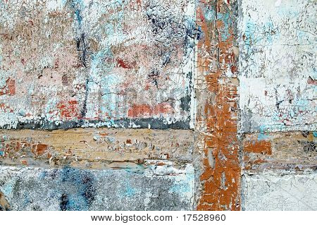 Thick paint and paster slowly peeling off and cracking on an antique wood, brick and plaster building.