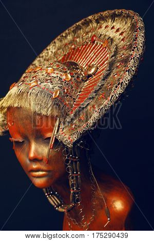 Mannequin head with metal headwear on black background