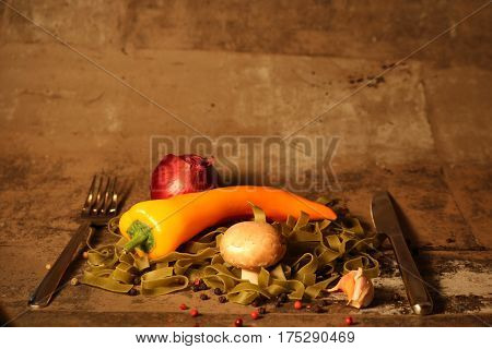 green pasta with ingredients on stone background