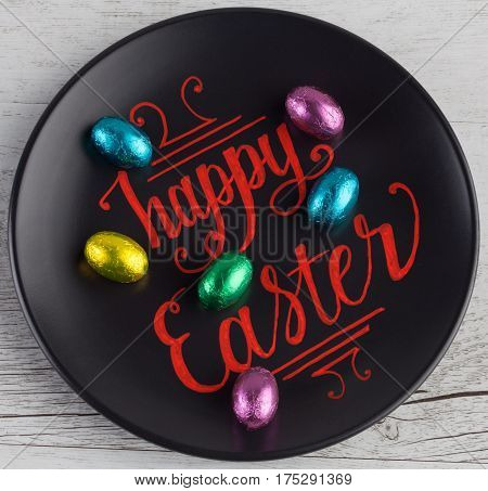 Happy Easter Hand Lettering Written In Red On Black Plate Decorated With Small Chocolate Easter Eggs