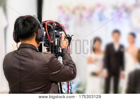 professional videographer recording wedding ceremony day with professional camcoder and boardcasting.
