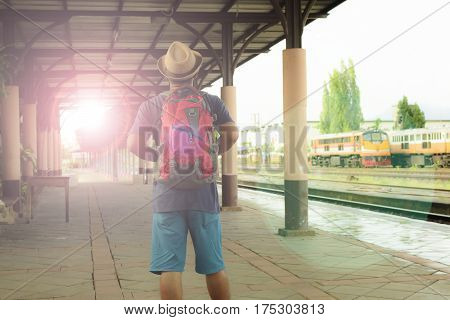 Hipster man backpack at train station.Back of male.