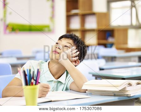 asian elementary schoolboy thinking while doing homework in classroom looking up hand on cheek.