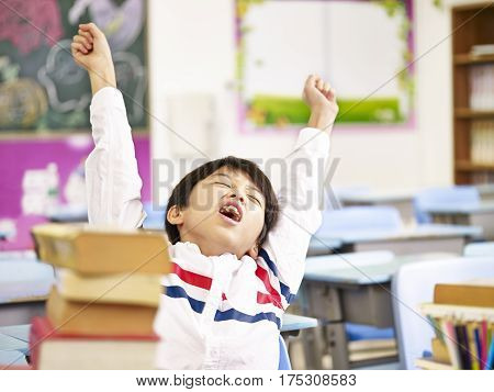 tired and exhausted asian elementary schoolboy stretching in classroom.