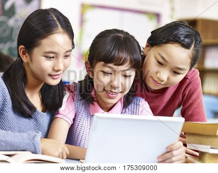 three asian elementary school girls friends looking at a tablet together during break in classroom.